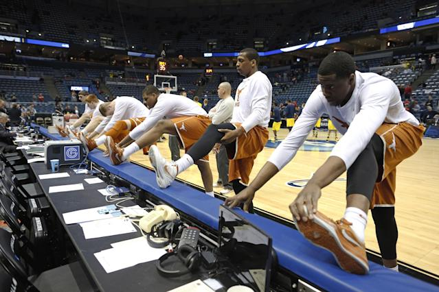 Texas players stretch before a third-round game against the Michigan of the NCAA college basketball tournament Saturday, March 22, 2014, in Milwaukee. (AP Photo/Jeffrey Phelps)