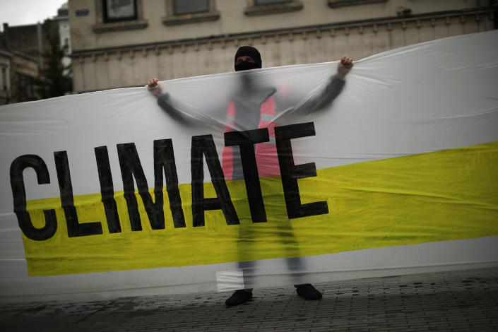 """A man, wearing a mask to prevent the spread of the coronavirus, holds a banner that reads: """"United for climate"""" during a small climate change protest in downtown Brussels, Friday, Sept. 25, 2020. (AP Photo/Francisco Seco)"""