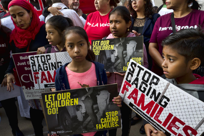 FILE - In this June 26, 2018, file photo, children stand and hold protest signs during a rally in front of Federal Courthouse in Los Angeles. More than 50 immigrant children under age 5 will be reunited with their parents by Tuesday's court-ordered deadline for action by Trump administration and the families will then be released into the U.S., a government attorney said Monday, July 9, 2018. (AP Photo/Richard Vogel, File)