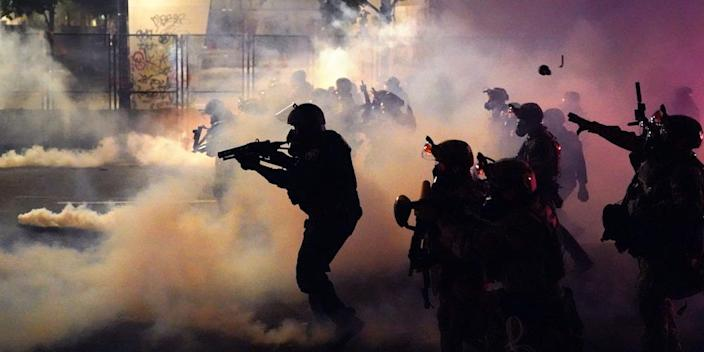 Federal officers deploy tear gas and less-lethal munitions while dispersing a crowd of about a thousand protesters on July 24 in Portland.