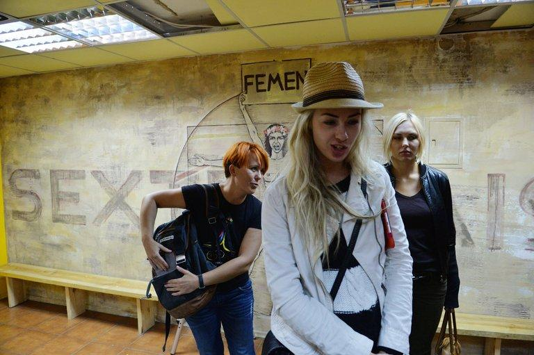 Activists from the Ukrainian feminist group FEMEN, Anna Hutsol (left), Oleksandra Shevchenko and Yana Zhdanova, stand in their office in Kiev on August 27, 2013. Ukrainian feminist movement Femen said Wednesday it was moving out of its Kiev offices, alleging official wiretapping, a day after police said they discovered a cache of illegal weapons in a raid of its premises