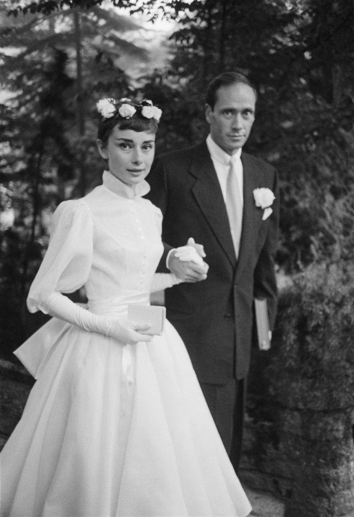 """<p>In a dress designed by Balmain, <a href=""""https://www.townandcountrymag.com/society/g2267/audrey-hepburn-images/"""" rel=""""nofollow noopener"""" target=""""_blank"""" data-ylk=""""slk:Audrey Hepburn"""" class=""""link rapid-noclick-resp"""">Audrey Hepburn</a>, then 25, married Mel Ferrer, 37, in Bürgenstock, Switzerland. They met at a cocktail party hosted by Hepburn's <em>Roman Holiday</em> costar Gregory Peck. The couple had a son together and then divorced in 1968. Hepburn remarried just once more.</p>"""