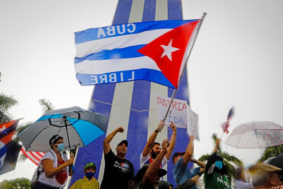 People demonstrate waving Cuban flags during a protest against the Cuban government at Tamiami Park in Miami, on July 13, 2021. - Washington warned Haitians and Cubans against trying to flee to the United States as they endure domestic unrest, saying the trip is dangerous and they would be repatriated. (Photo by Eva Marie UZCATEGUI / AFP) (Photo by EVA MARIE UZCATEGUI/AFP via Getty Images)