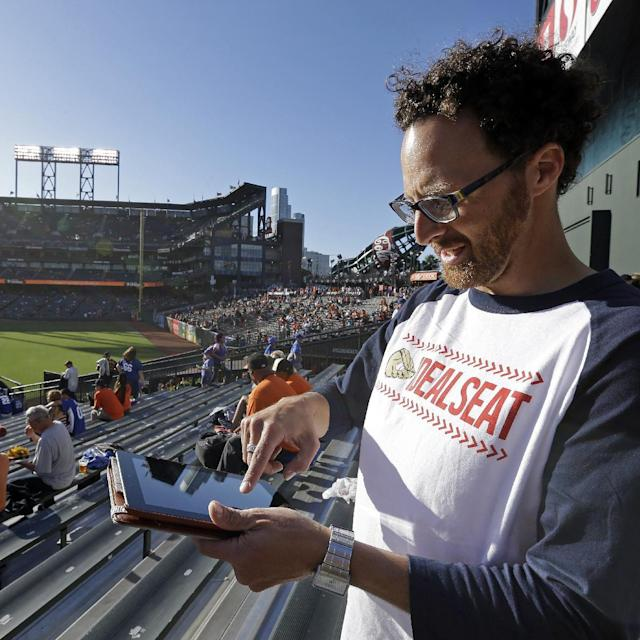 In this photo taken Friday, July 25, 2014, Joel Carben enters information into his tablet while standing in the bleacher seats in right field prior to a baseball game between the Los Angeles Dodgers and the San Francisco Giants at AT & T Park in San Francisco. Carben has designed mobile foul ball tracking system software designed to increase a fan's chances of catching a foul ball at baseball games. (AP Photo/Ben Margot)