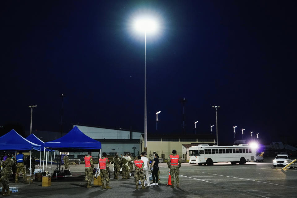 A bus carrying people flown out of Afghanistan heads to the medical screening station at Ramstein Air Base, in Ramstein-Miesenbach, Germany, Friday, Aug. 20, 2021. (Uwe Anspach/dpa via AP)