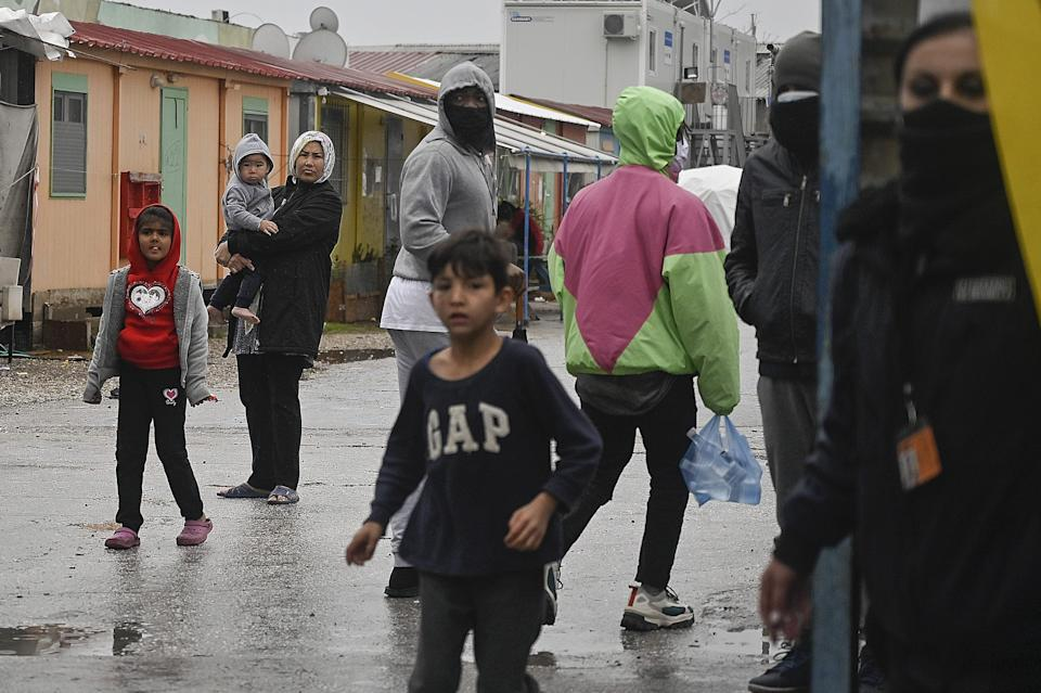 Refugees look on from the Eleonas camp during a demonstration by solidarity groups calling for enrolment of all the refugee children to public schools and equal rights to education.in Athens on February 14, 2021. - Amid the lockdown in the country which affects the refugee camps, only some 5000 refugee children from 31,000 living in Greece attend schools or online education, according to KEERFA (Movement United Against Racism). (Photo by LOUISA GOULIAMAKI / AFP) (Photo by LOUISA GOULIAMAKI/AFP via Getty Images)