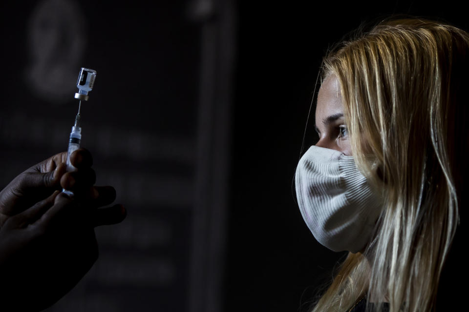 A healthcare worker shows Maria Rosa Machado her dose of the Pfizer COVID-19 vaccine before she is inoculated, on the first day of a vaccination campaign for 17-year-olds, at a vaccination center in Rio de Janeiro, Brazil, Thursday, Aug. 26, 2021. (AP Photo/Bruna Prado)