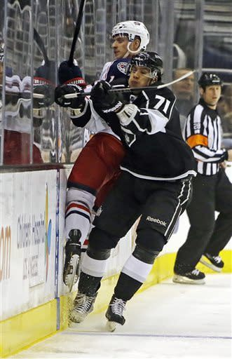 Los Angeles Kings center Jeff Carter (77) and Columbus Blue Jackets left wing Matt Calvert (11) slam into the boards in the first period of an NHL hockey game in Los Angeles Thursday, April 18, 2013. (AP Photo/Reed Saxon)