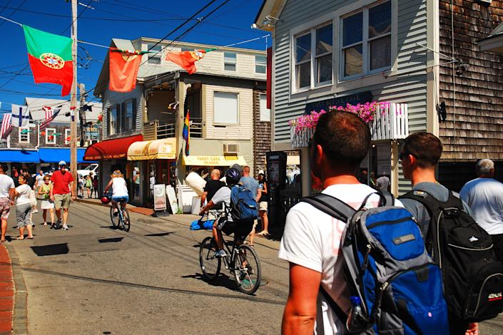 people biking and walking through a small street in Provincetown