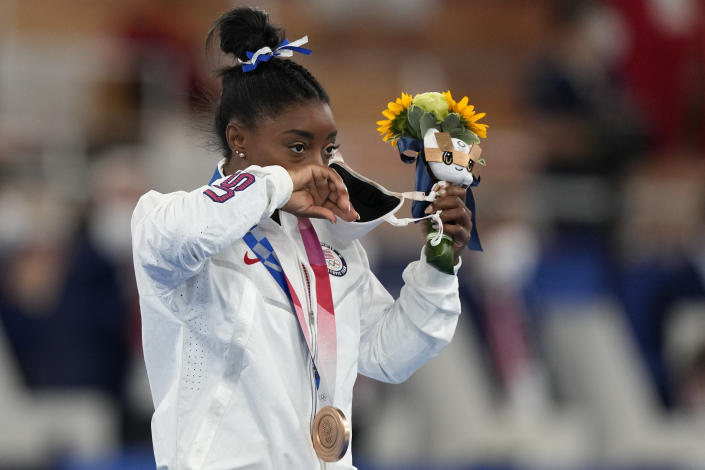 Simone Biles, of the United States, removes her face mask on the podium after winning the bronze medal on the balance beam during the artistic gymnastics women's apparatus final at the 2020 Summer Olympics, Tuesday, Aug. 3, 2021, in Tokyo, Japan. (AP Photo/Natacha Pisarenko)