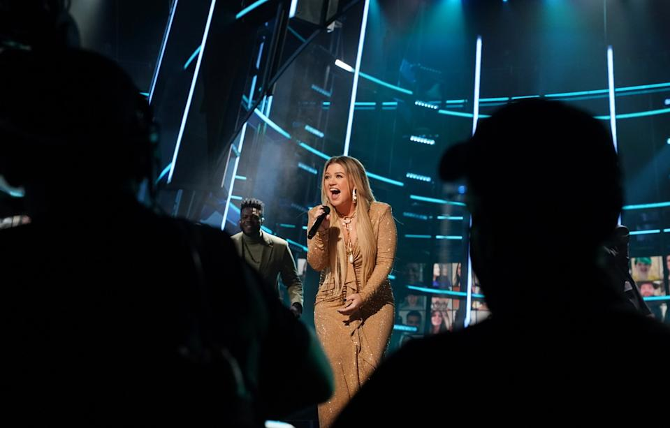 Kelly Clarkson signs on stage at the 2020 Billboard Music Awards