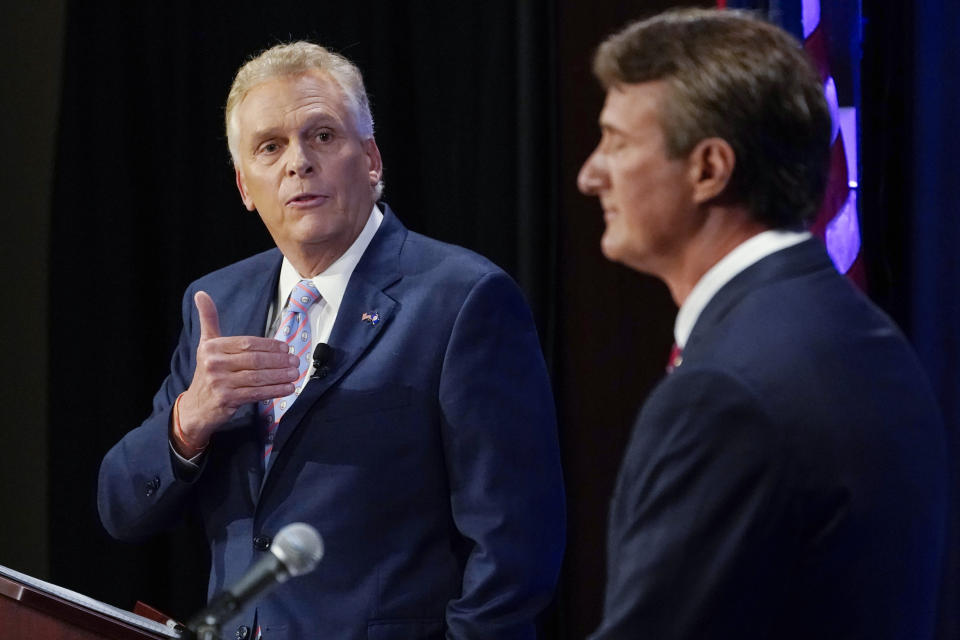 FILE - In this Sept. 16, 2021, file photo Democratic gubernatorial candidate former Governor Terry McAuliffe, left, gestures as Republican challenger, Glenn Youngkin, listens during a debate at the Appalachian School of Law in Grundy, Va. Polls suggest the race is close, adding to McAuliffe's sense of urgency to campaign on a robust list of his party's accomplishments. The McAuliffe campaign confirmed Tuesday that Biden and former President Barack Obama would rally voters in the state later in the month at separate events. (AP Photo/Steve Helber, File)