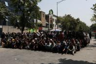 Afghans wait to visit a bank on a street in Kabul