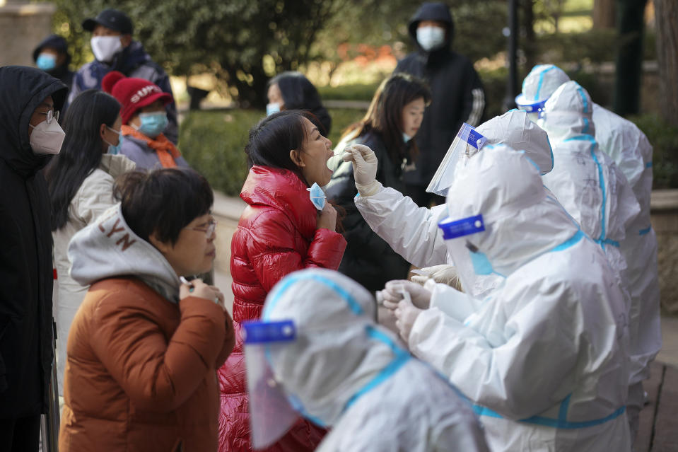 In this photo released by Xinhua News Agency, medical workers in a protective suits take swab from residents near a residential area in Shijiazhuang in north China's Hebei province on Wednesday, Jan. 6, 2021. Lockdown measures were being imposed in a northern Chinese province where coronavirus cases more than doubled in the region near Beijing that's due to host some events in next year's Winter Olympics. (Mu Yu/Xinhua via AP)