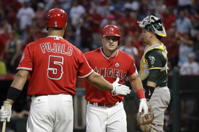 Los Angeles Angels' Mike Trout (center) celebrates his home run with Albert Pujols (left). (AP)