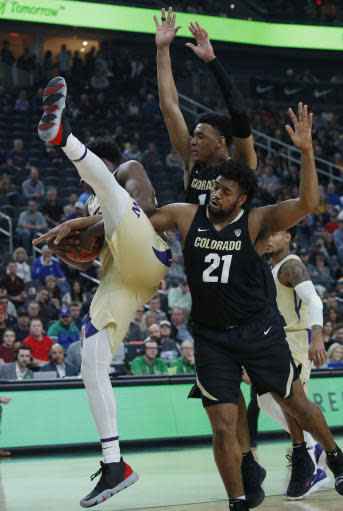 From left, Washington's Noah Dickerson, Colorado's Tyler Bey and Evan Battey (21) vie for a rebound during the first half of an NCAA college basketball game in the semifinals of the Pac-12 men's tournament Friday, March 15, 2019, in Las Vegas. (AP Photo/John Locher)