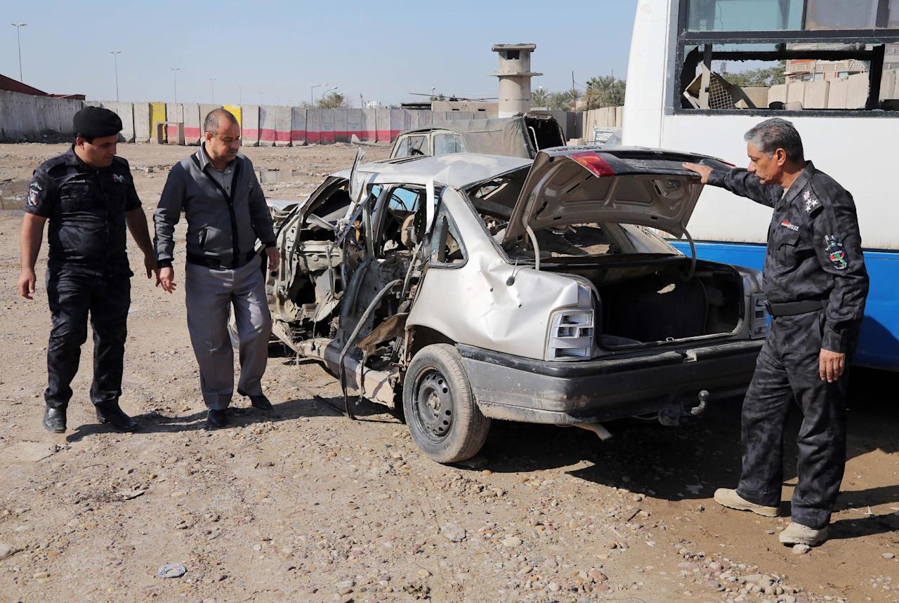 Iraqi security forces inspect a car destroyed after a car bomb attack in the Jamila neighborhood of Baghdad, Iraq, Thursday, Feb. 6, 2014. A string of car bomb attacks hit commercial areas in Baghdad on Thursday, killing and wounding scores of people, said Iraqi officials. (AP Photo/Karim Kadim)