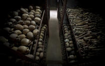 """FILE - In this Friday, April 4, 2014 file photo, the skulls and bones of some of those who were slaughtered as they sought refuge inside the church, are laid out on shelves in an underground vault as a memorial to the thousands who were killed in and around the Catholic church during the 1994 genocide in Nyamata, Rwanda. France's role before and during 1994's Rwandan genocide was a """"monumental failure"""" that the country must face, the lead author of a sweeping report commissioned by President Emmanuel Macron said, as the country is about to open its archives from this period for the first time to the broader public.(AP Photo/Ben Curtis, File)"""