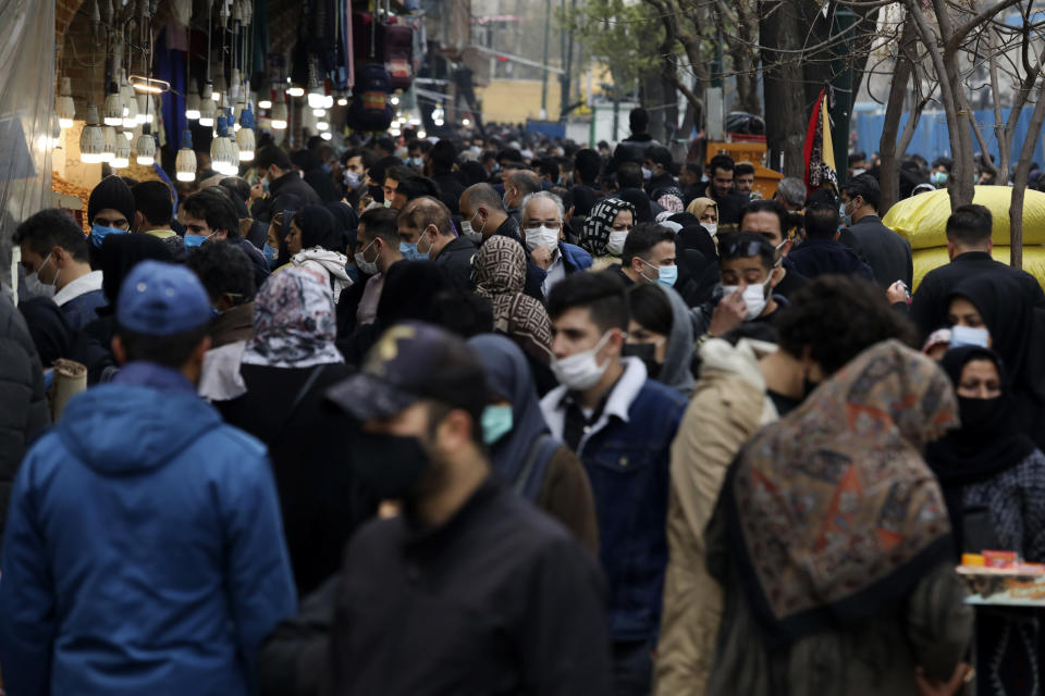"""Mask-clad shoppers walk at Tehran's Grand Bazaar, ahead of the Persian New Year, or Nowruz, meaning """"New Day."""" Iran, Monday, March 15, 2021. (AP Photo/Vahid Salemi)"""