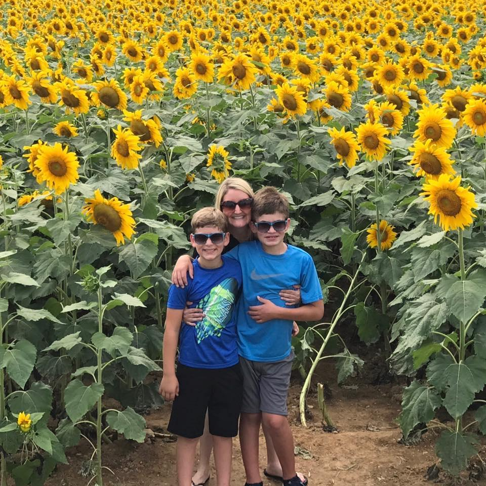 Connor Dobbyn is seen with his mum and brother in a sunflower field.