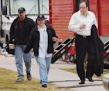 <p>Gandolfini leaves a trailer with coffee, on his way to set with two crew members. </p>