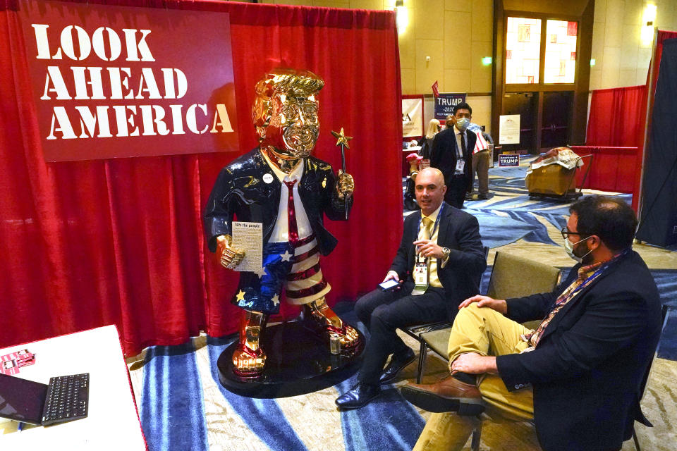 Look Ahead America sponsor Matt Braynard, center, talks to conference attendees at his booth in the merchandise show with a statue of former president Donald Trump at the Conservative Political Action Conference (CPAC) Friday, Feb. 26, 2021, in Orlando, Fla. (AP Photo/John Raoux)