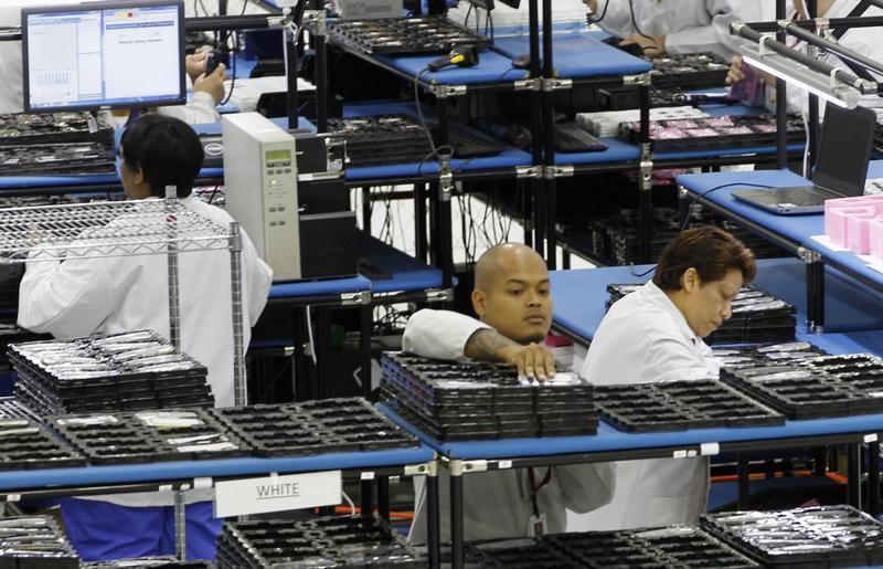 """Workers assemble Motorola phones at the Flextronics plant that will be building the new Motorola smart phone """"MotoX"""" in Fort Worth, Texas September 10, 2013. REUTERS/Mike Stone"""