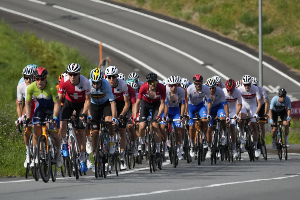 Athletes in the peloton climb during the men's cycling road race at the 2020 Summer Olympics, Saturday, July 24, 2021, in Oyama, Japan. (AP Photo/Christophe Ena)