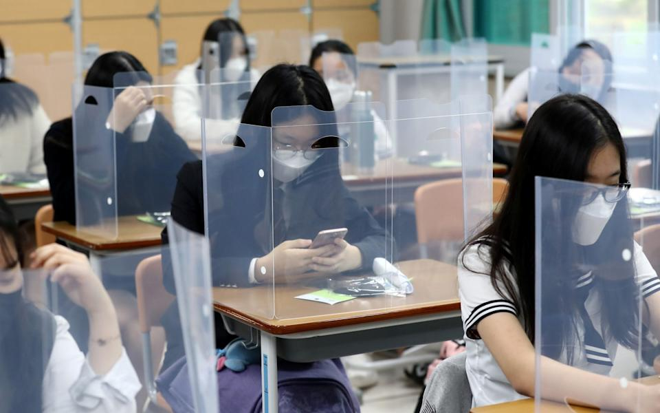 High school students wearing face masks prepare for classes, with plastic covers placed on desks to prevent infection - YONHAP /via REUTERS