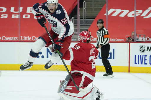 Columbus Blue Jackets left wing Eric Robinson (50) jumps to screen Detroit Red Wings goaltender Thomas Greiss (29) in the first period of an NHL hockey game Monday, Jan. 18, 2021, in Detroit. (AP Photo/Paul Sancya)