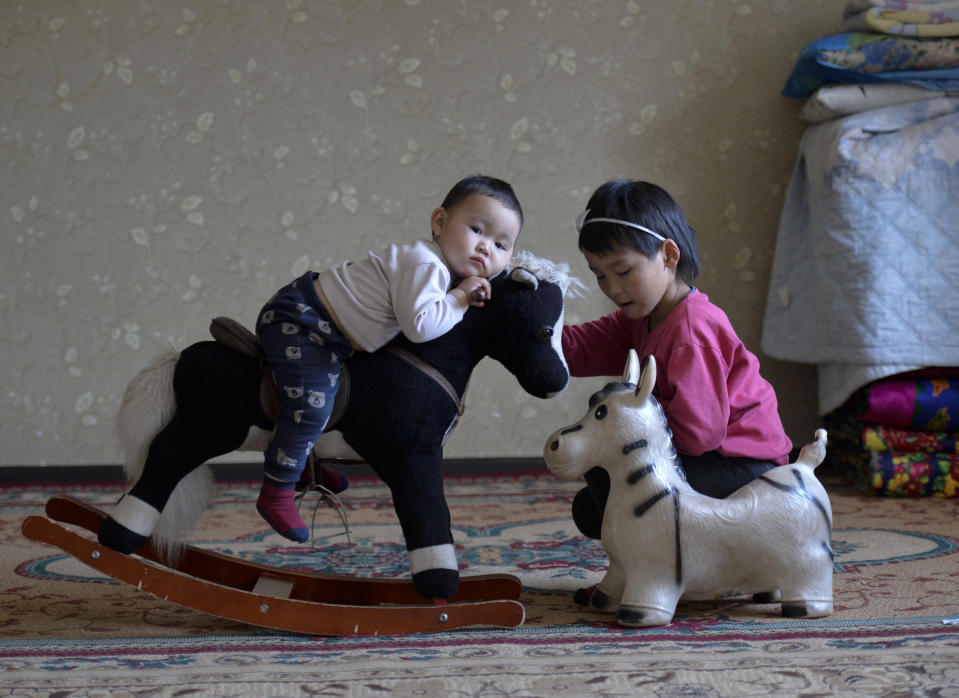 Kanat Kaliyev's son Adilet's daughters Aibike, right, and Aima play at the family house in Tash Bashat village, about 24 kilometers (15 miles) southeast of Bishkek, Kyrgyzstan, Saturday, Oct. 17, 2020. Political turmoil has gripped Kyrgyzstan over recent years, but life in this quiet village nestled between scenic mountains follows its centuries-old course.(AP Photo/Vladimir Voronin)