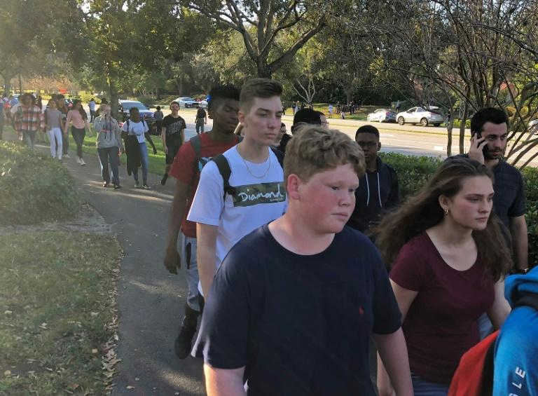 Students leave Marjory Stoneman Douglas High School in Parkland, Florida, after a gunman opened fire on campus