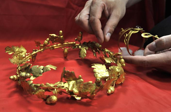 A police officer displays the wreath of gold oak leaves and acorns, and the gold arm band with carved snake heads at the ends date from roughly the 4th Century B.C. in Thessaloniki on Friday June 8, 2012. A 60-year-old retired policeman and a 41-year-old painter _ were arrested late the previous night east of the city after the artifacts were found during a routine traffic check. (AP Photo/Nikolas Giakoumidis)