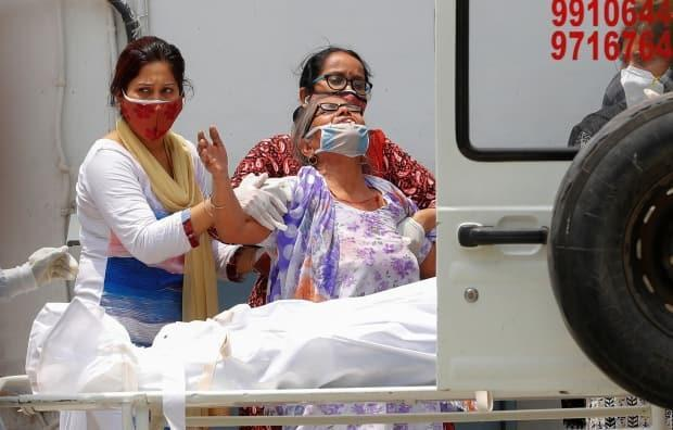 A woman mourns after seeing the body of her son who died due to the coronavirus disease, outside a mortuary of a COVID-19 hospital in New Delhi on May 12.