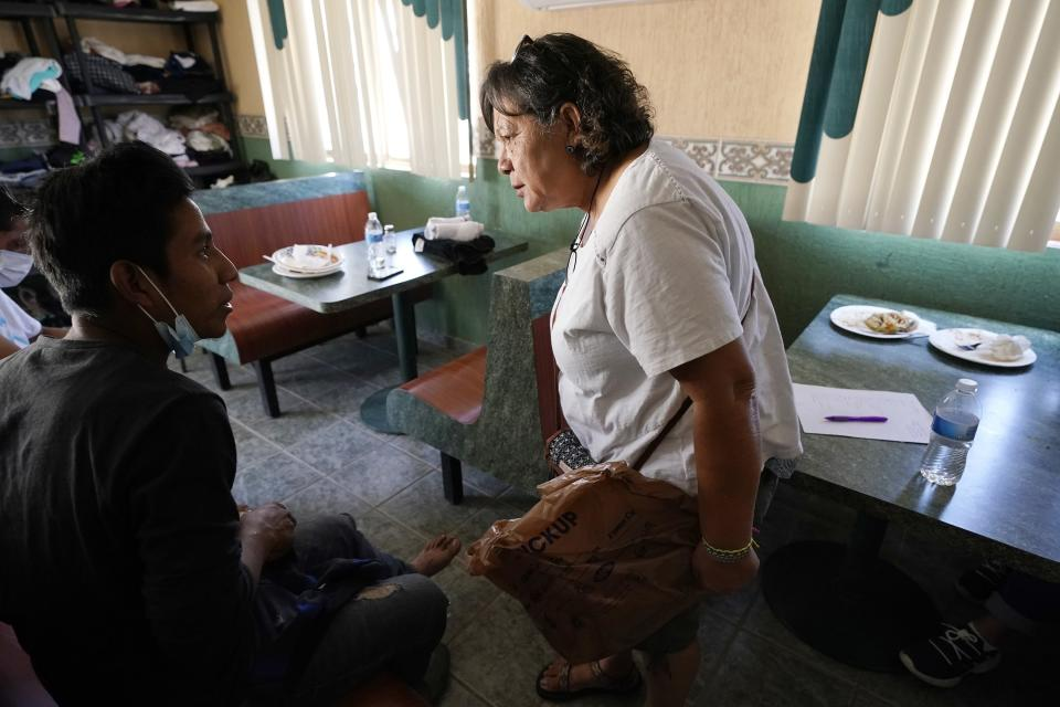 Dora Rodriguez, center, who was among 13 Salvadorans who survived in 1980 when another 13 people in the group died in the broiling sun near Organ Pipe Cactus National Monument, talks with Vicente Lopez, 19, who grew up in Guatemala's Ixil triangle, where government troops in the early 1980s wiped out entire communities suspected of harboring rebels, on Wednesday, May 19, 2021, in Sasabe, Mexico. At the age of 19, she remained in Tucson and eventually became a U.S. citizen. (AP Photo/Ross D. Franklin)