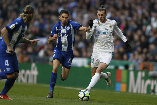 Real Madrid's Gareth Bale, right, tussles for the ball with Alaves' Ruben Sobrino, centre, during the Spanish La Liga soccer match between Real Madrid and Alaves at the Santiago Bernabeu stadium in Madrid, Saturday, Feb. 24, 2018. Bale scored once in Real Madrid's 4-0 victory. (AP Photo/Francisco Seco)