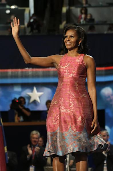 FILE - In this Sept. 4, 2012 file photo, first lady Michelle Obama waves to delegates at the Democratic National Convention in Charlotte, N.C. Obama's dress was designed by Tracy Reese. Obama has proven her fashion savvy time and time again since she was introduced to the country as first lady on Inauguration Day 2009. In the past four years she has adeptly walked the line between directional fashionista and everywoman. (AP Photo/Charles Dharapak, File)