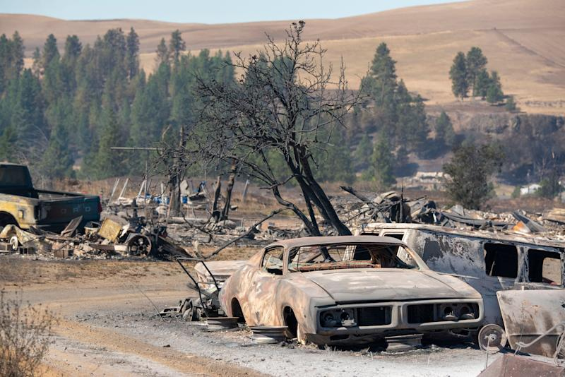 Vehicles are destroyed by a wildfire that swiftly moved through Maldin, Washington, on Tuesday. (Photo: ASSOCIATED PRESS)