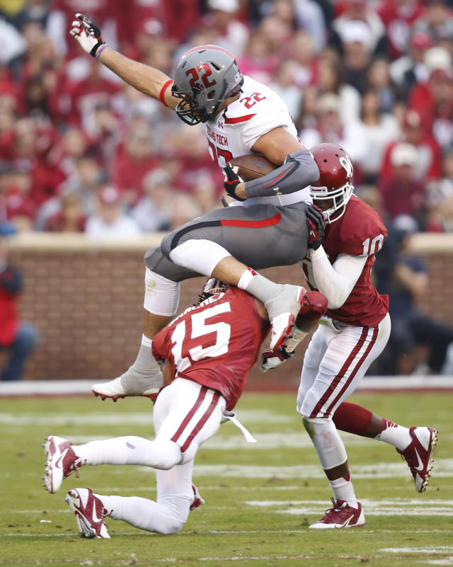 Texas Tech tight end Jace Amaro (22) jumps over Oklahoma defensive back Zack Sanchez (15) in the second quarter of an NCAA college football game in Norman, Okla., Saturday, Oct. 26, 2013. Oklahoma defensive back Quentin Hayes (10) is at right. (AP Photo/Sue Ogrocki)