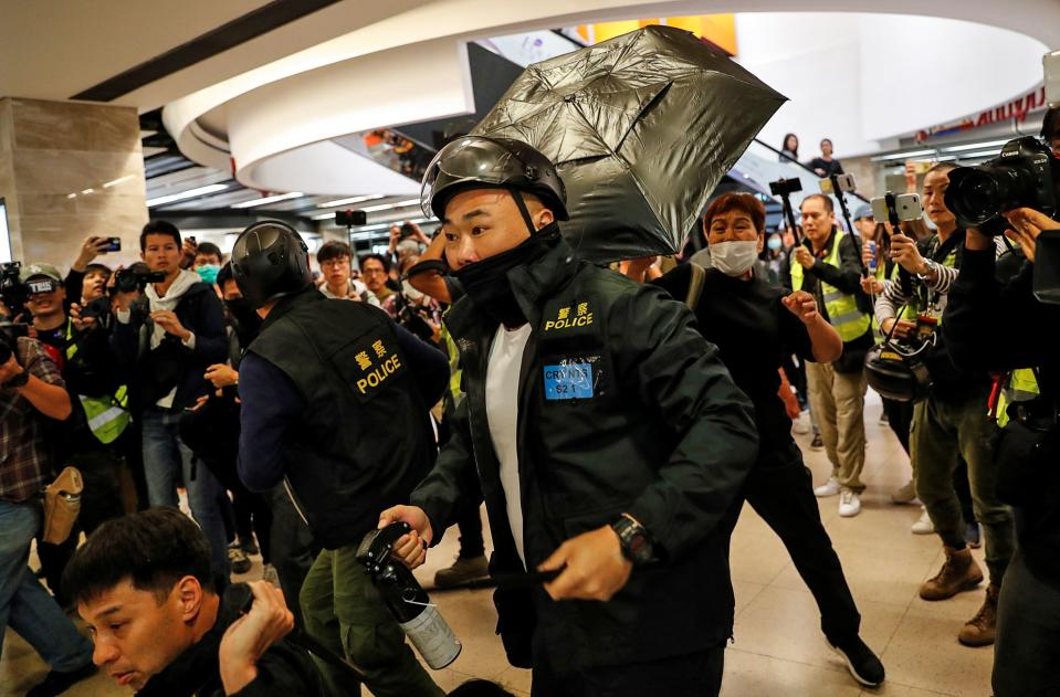 A woman hits a police officer with an umbrella as others detain an anti-government protester during a demonstration inside a mall in Hong Kong, China December 15, 2019. REUTERS/Danish Siddiqui