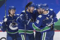 From left to right, Vancouver Canucks' Quinn Hughes, Tanner Pearson, Bo Horvat and Nils Hoglander, of Sweden, celebrate Horvat's goal during the second period of an NHL hockey game against the Toronto Maple Leafs in Vancouver, British Columbia, Sunday, April 18, 2021. (Darryl Dyck/The Canadian Press via AP)