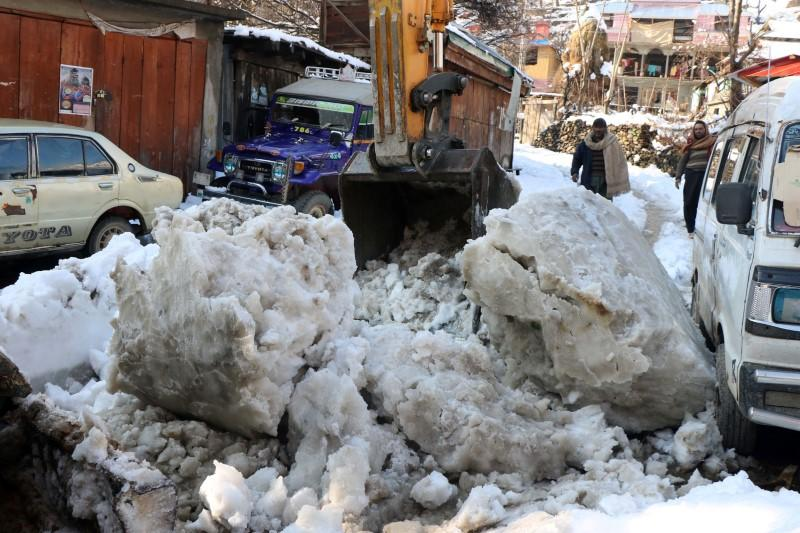 Residents stand as an excavator removes the snow boulders on a road after a heavy snowfall in Neelum Valley