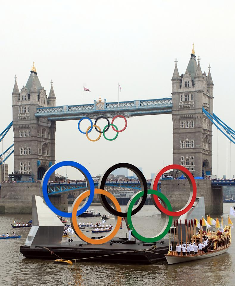 In this handout image provided by LOCOG, Torchbearer 018 Amber Charles stands underneath the giant Olympic Rings on the River Thames outside City Hall during Day 70 of the London 2012 Olympic Torch Relay  on July 27, 2012 in London, England. The Olympic Flame is now on Day 70 of a 70-day relay involving 8,000 torchbearers covering 8,000 miles.  (Photo by LOCOG via Getty Images)