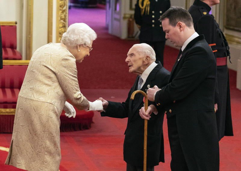 Britain's Queen Elizabeth wears gloves as she awards the MBE (Member of the Order of the British Empire) to Harry Billinge from St Austell, during an investiture ceremony at Buckingham Palace in London, Tuesday March 3, 2020. Buckingham Palace declined to confirm whether the Queen was taking the precaution because of the coronavirus outbreak. (Dominic Lipinski/PA via AP)