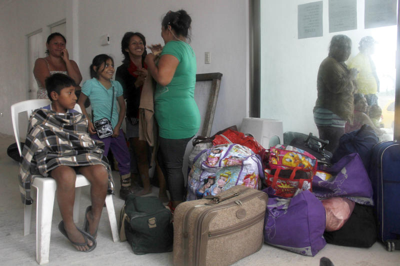 Residents arrive at a shelter in Mahahual, Mexico, Tuesday, Aug. 7, 2012 as Tropical Storm Ernesto is expected to slam into the Caribbean coast as a hurricane late Tuesday. The heart of the storm was expected to hit south of Cancun and the Riviera Maya and officials prepared shelters there as a precaution. (AP Photo/Israel Leal)