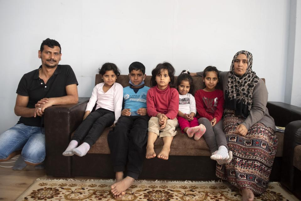 Abdul Salam Al Khawien, 37, left, and his wife Kariman, 32, right, pose with their children for a family photo, at their apartment in the northern city of Thessaloniki, Greece, Saturday, May 1, 2021. Sundered in the deadly chaos of an air raid, a Syrian family of seven has been reunited, against the odds, three years later at a refugee shelter in Greece's second city of Thessaloniki. (AP Photo/Giannis Papanikos)