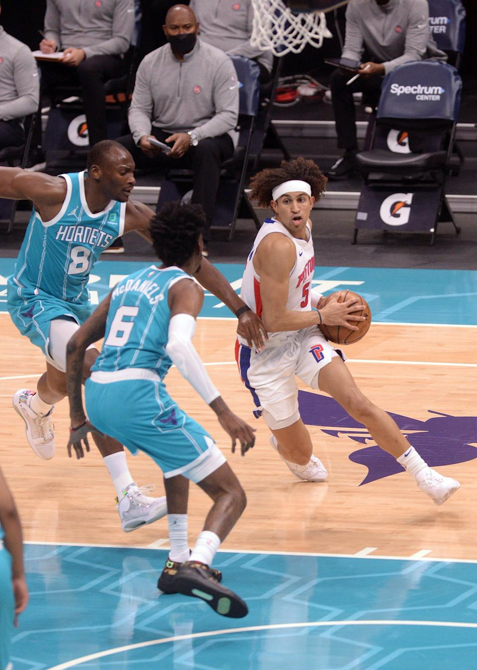 Detroit Pistons guard Frank Jackson (5) drives against Charlotte Hornets center Bismack Biyombo (8) and forward Jalen McDaniels (6) during the first half on May 1, 2021 at the Spectrum Center.