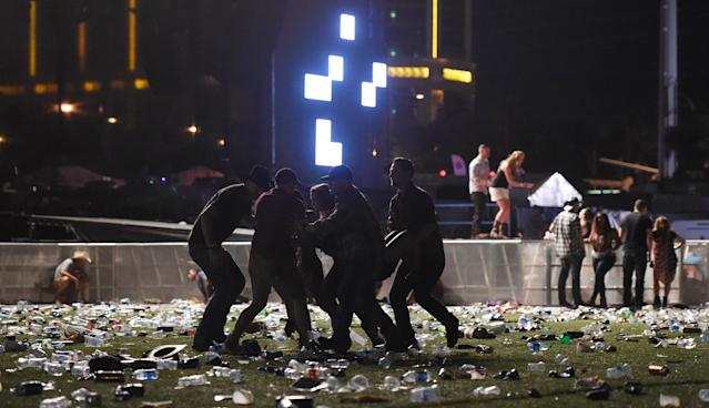 <p>People carry a person at the Route 91 Harvest country music festival after apparent gun fire was heard on Oct. 1, 2017 in Las Vegas, Nevada. There are reports of an active shooter around the Mandalay Bay Resort and Casino. (Photo: David Becker/Getty Images) </p>