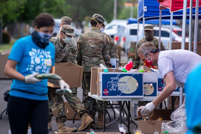 United Food Bank volunteers and National Guard soldiers prepare food boxes for families on April 17 at the Mesa Convention Center in Mesa, Ariz.