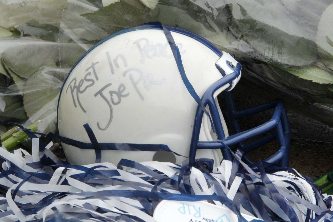 A miniature football helmet rests among flowers left at the foot of a statue of Joe Paterno outside Beaver Stadium on the Penn State University campus after learning of his death on Sunday, Jan. 22, 2012, in State College,Pa. (AP Photo/Gene J. Puskar)